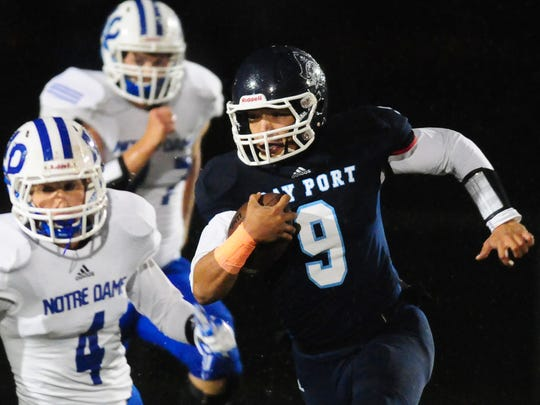 Bay Port quarterback Alec Ingold gets past Notre Dame Academy's Vincent Pallini on a first quarter run in the FRCC game played at Goelz Field in Ashwaubenon, Friday, September 12, 2014.