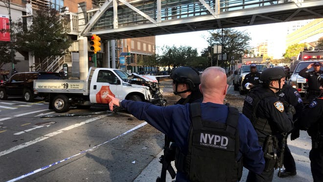 In this photo provided by the New York City Police Department, officers respond to a report of gunfire along West Street near the pedestrian bridge at Stuyvesant High School in lower Manhattan in New York, Tuesday, Oct. 31, 2017.
