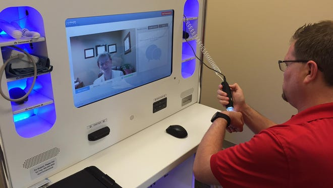 """Jay Moore, MD, senior clinical officer for Anthem, demonstrates how the """"derm cam"""" on the LiveHealth Online kiosk at Croley XXX. The online tele-health services can also be accesses on your smart phone, tablet or computer."""