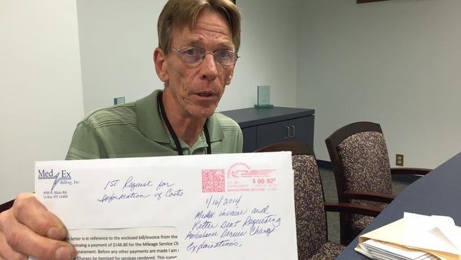 Chris Uhl, 62, of Henrietta, displays one of the many letters he has written to try to interpret his $1,139 ambulance bill.