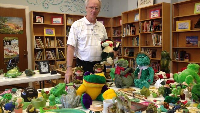 The Rev. Lee Weems, the retiring associate pastor at Emmanuel Baptist Church, poses in the church library beside hundreds of artificial frogs he has collected over the years. He's giving them all away except the one he's holding, which has special sentimental value.