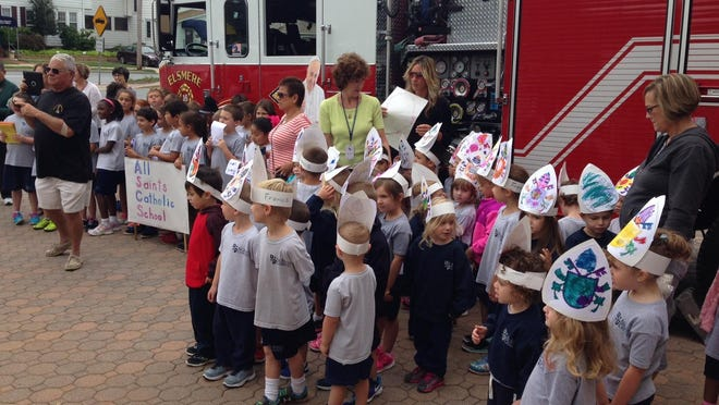 In anticipation of the coming Philadelphia visit by Pope Francis, students from All Saints Catholic School in Elsmere on Tuesday visit the Elsmere Fire Company on Kirkwood Highway as part of a walk-around tour singing songs about faith and the pontiff.