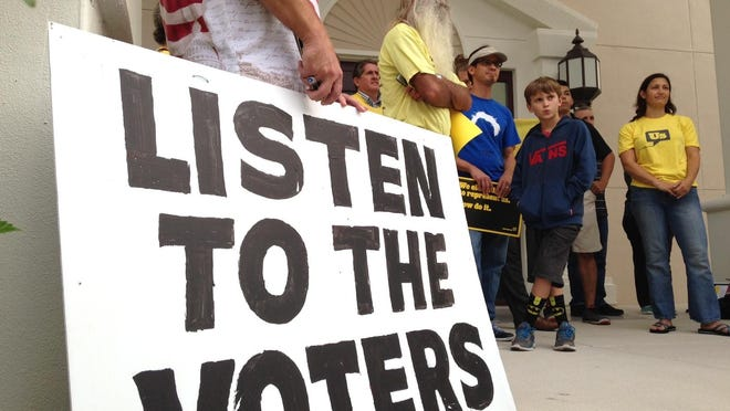 More than a dozen members of Represent the Space Coast came out to Cocoa City Hall to protest corruption.