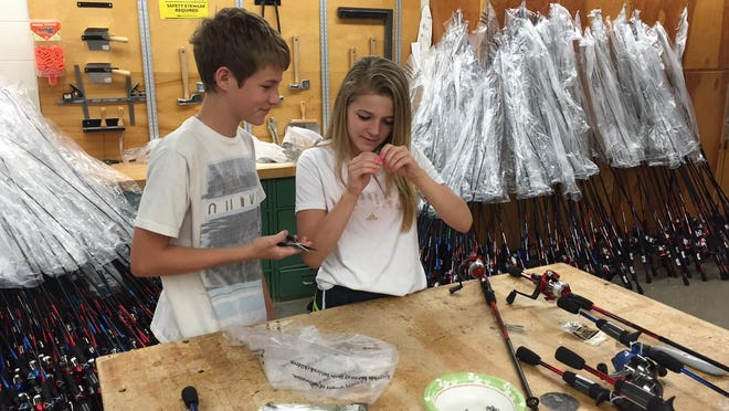 Dominick Zolnar and Kiaunna Cislo work on putting rod and reels together at North Middle School Wednesday.