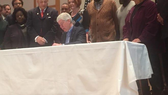 Gov. Rick Snyder signs safe water legislation Friday as Rep. Sheldon Neeley, D-Flint, the bill's sponsor, looks on.