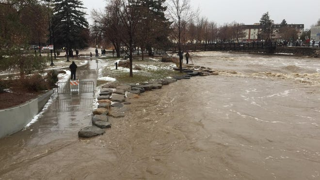 The Truckee River laps over the sidewalk in Wingfield Park.