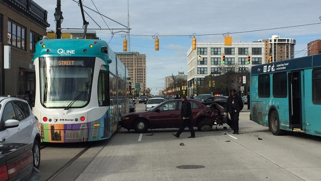 A bus collided with a car on southbound Woodward Avenue, forcing the car into a QLine train near the Canfield stop.