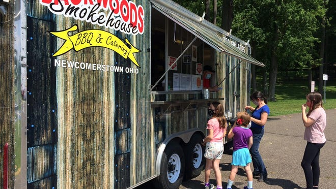 A Newcomerstown family lines up to order at Backwood Smokehouse at Cy Young Park Thursday afternoon.