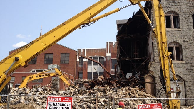 Heavy machinery helps tear down a former convent in downtown Camden. The site, owned by the Diocese of Camden, will become a parking lot.