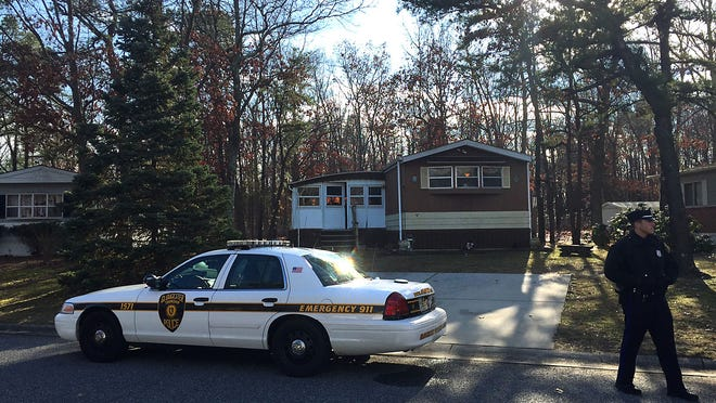 Gloucester Township police stand outside the home of Susan D. Johnson, a Gloucester Township woman who was reported missing Thursday and was found slain Friday in a wooded area in Evesham