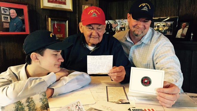 Battle of Iwo Jima veteran John Lauriello of Haddon Township (center), son Paul (right ) and grandson Talon (left) read dozens of letters received from well wishers around the U.S. and abroad who sent donations so the family could head to the Pacific island for the anniversary of the battle in 1945. The former Marine was in the first wave to land on the beach in a fierce battle that lasted weeks and cost thousands of Marine lives.