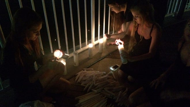 Nikoletta Pappas, left, lights candles before the start of a vigil to remember Austin Vonckx.