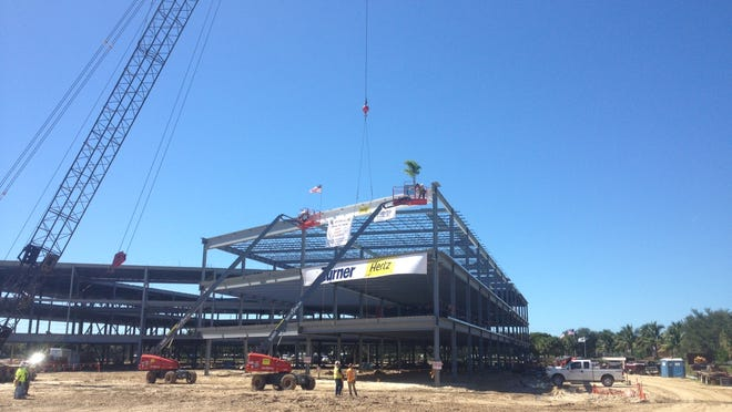Workers from Turner Construction put the last beam in place Thursday of the three-story main headquarters building of Hertz in Estero.