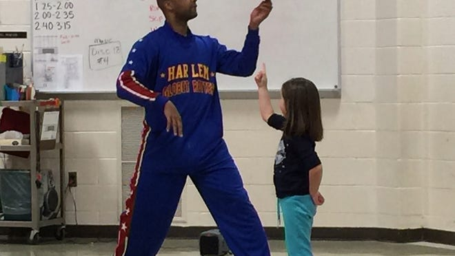 """""""Flight Time"""" Lang spins a ball before placing it on the finger of a Wilcox Elementary student during an assembly."""