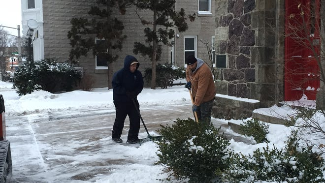 Anthony Agudelo Jr. (left) and Juan Marin got an early start Tuesday clearing snow around the United Methodist Church in Morristown.