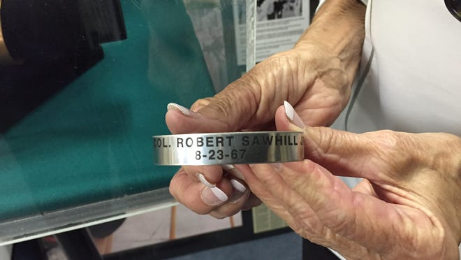 Monnie Lutz holds a POW/MIA bracelet bearing the name of Lt. Col. Robert Sawhill Jr. She donated the bracelet to the museum on Monday.
