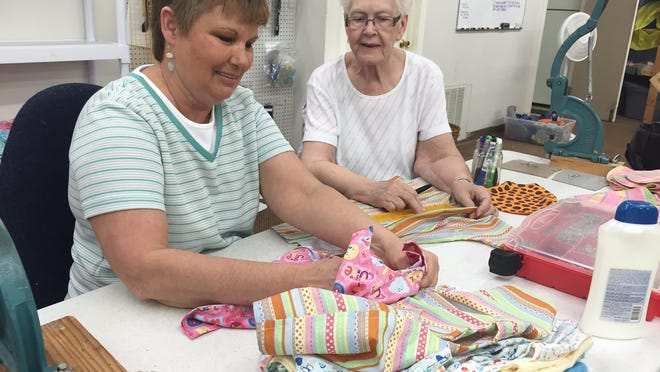 Volunteers Deb Isom and Virginia Kincaid sew bibs. About 50 percent of items given to newborns are handmade by volunteers.