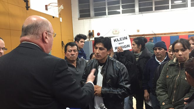 School Superintendent Joel Klein, left, speaks to Latino residents after an East Ramapo school board meeting Tuesday.