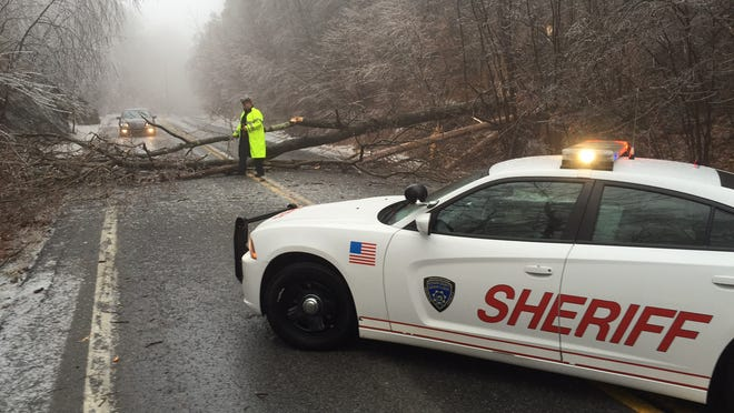A Putnam County sheriff's deputy sets flares on Route 301 in Kent where a tree fell and blocked the road about 1 mile west of the Taconic Parkway, Dec. 9, 2014.