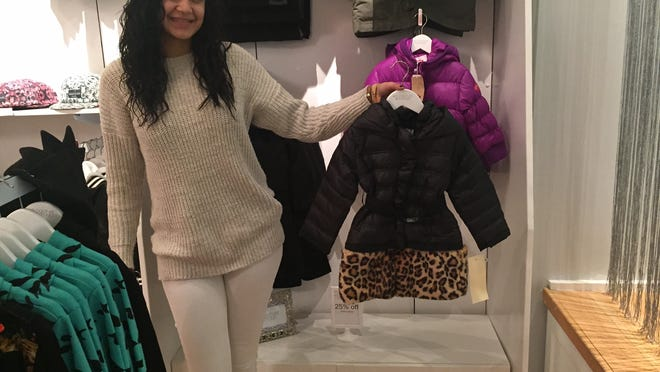 Kiara Jaquez holds the Down American Widgeon Black 2 Way coat at Kid Couture Boutique which opened 6 weeks ago at the Palisades Center in West Nyack.