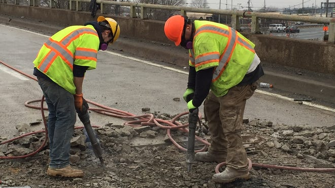 Workers repair potholes on the Del. 141 bridge over U.S. 13 in March 2015
