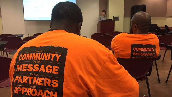 Various members of splinter groups of Chicago's Cure Violence group listen to best practices on how to track their efforts during training in Wilmington.