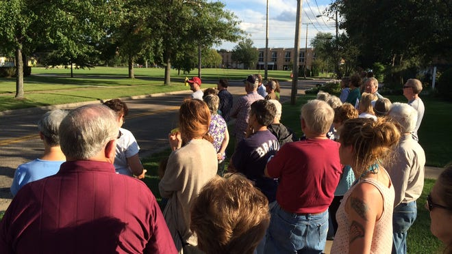 Walk participants listen to Phil Brown during the Wednesday Walkabout on Third Street.