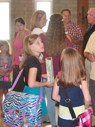 Emma Wallace (left) and her sister Avery Wallace brought their book bags to Clough United Methodist Church for the annual backpack blessing to celebrate the beginning of the school year.