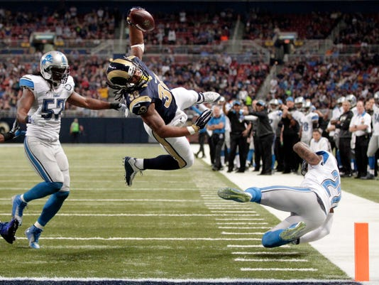 FILE - In this Dec. 13, 2015, file photo, St. Louis Rams running back Todd Gurley, center, scores between Detroit Lions linebacker Josh Bynes, left, and free safety Glover Quin on a 5-yard run during an NFL football game in St. Louis. The Rams' offense is built around second-year running back Todd Gurley, the NFL's offensive rookie of the year in 2015. (AP Photo/Tom Gannam, File)