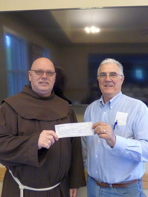 Friar Mike Jones, parochial vicar of St. Mary of the Angels Church in Anderson, accepts a check from Knights of Columbus activity representative Michael Massey.