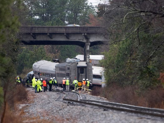 Workers are seen at the site of the Amtrak passenger