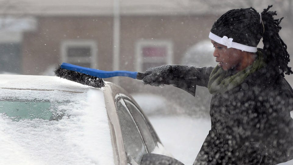 Pamela Oduho, 26, cleans ice and snow from her car