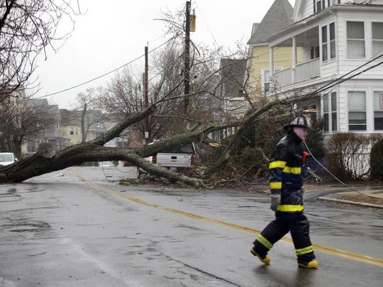 A firefighter walks at the scene of an uprooted tree blocking a residential street after downing a power line Friday, March 2, 2018 in Swampscott, Mass. as a major nor'easter pounds the East Coast, packing heavy rain, intermittent snow and strong winds. The Eastern Seaboard is expected to be buffeted by wind gusts exceeding 50 mph, with possible hurricane-strength winds of 80 to 90 mph on Cape Cod. (AP Photo/Elise Amendola)