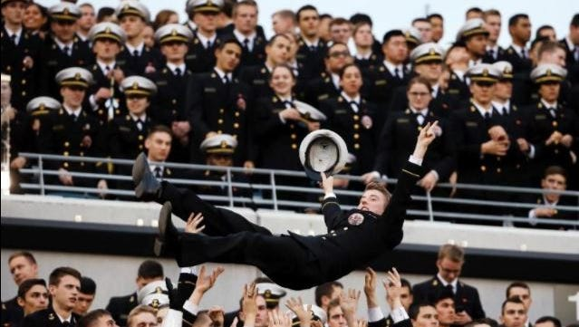 A Navy Midshipman is tossed in the air as Navy fans celebrate a touchdown during an NCAA college football game against Army and Saturday, Dec. 12, 2015, in Philadelphia.