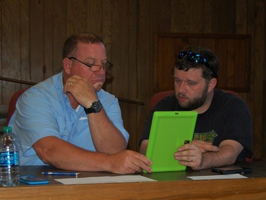 Marion County Justices of the Peace Gregg Alexander (left) and Carl McBee Jr. review bond issue documents on McBee's tablet during Tuesday night's Law Enforcement Committee meeting. The committee decided to present the Quorum Court with a proposal for a half-cent sales tax increase that would fund the construction of a new 60-bed jail.