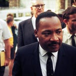 National tensions running high, Martin Luther King gets a police escort into Anderson Auditorium at the request of the Rev. Malcolm Calhoun (center, in glasses) on Aug. 21, 1965.