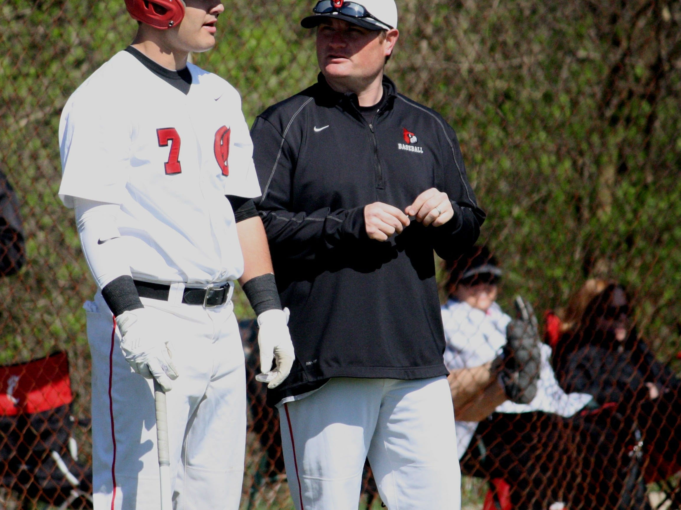During a pitching change, sophomore Jake Bolden, left, talks with first-year coach Justin Yeary at third base in a 13-0 win against Sycamore on April 11.