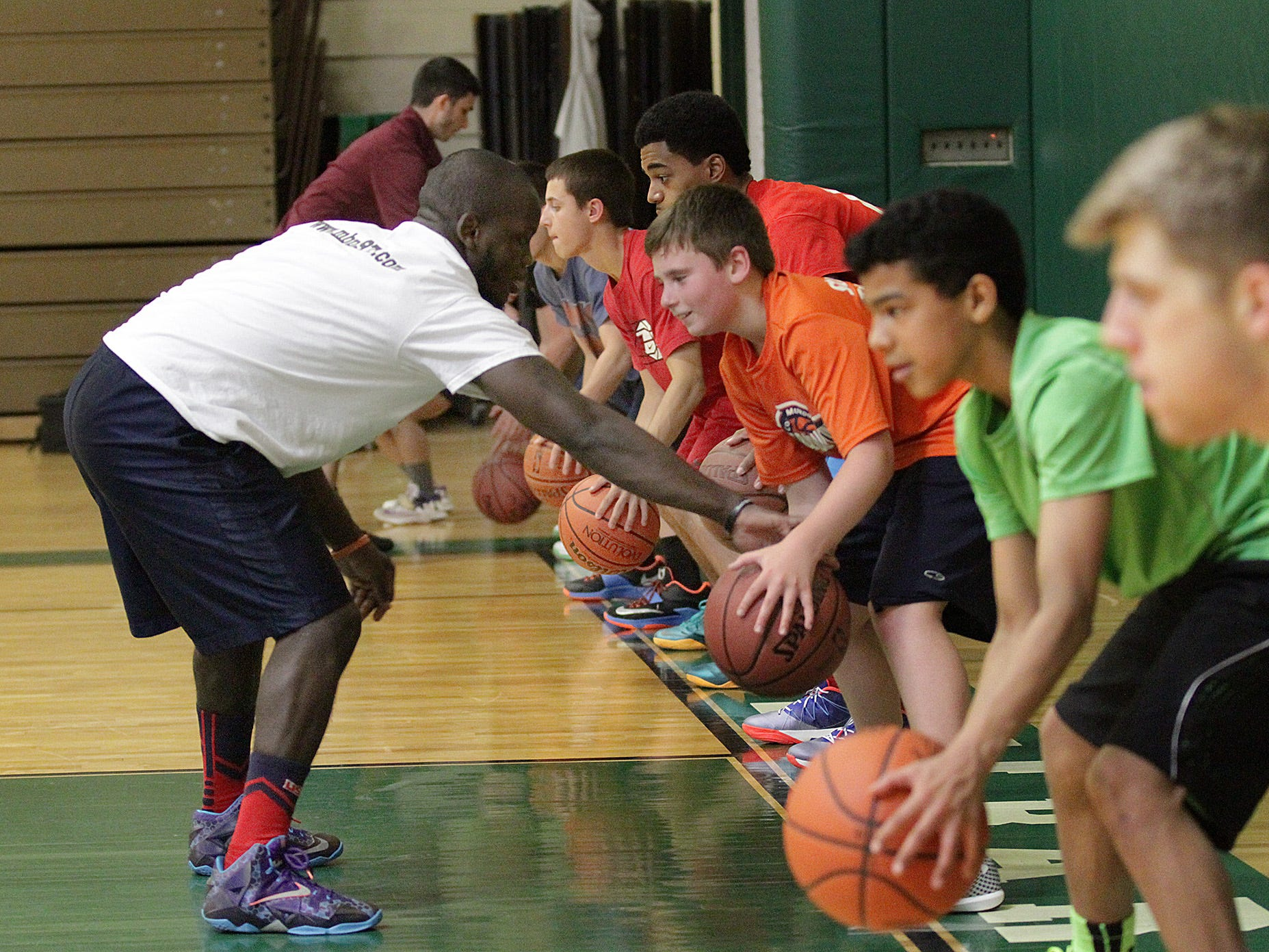 Lloyd Castello, one of the coaches at the Morris Basketball Program clinic, hassles players during a dribbling drill.