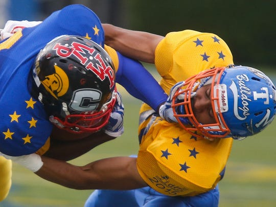 Blue's Reggie Carroll of William Penn, left, is brought down after a gain by Gold's Shane Leatherbury of Delmar High School in the first quarter of the DFRC Blue-Gold game Saturday.