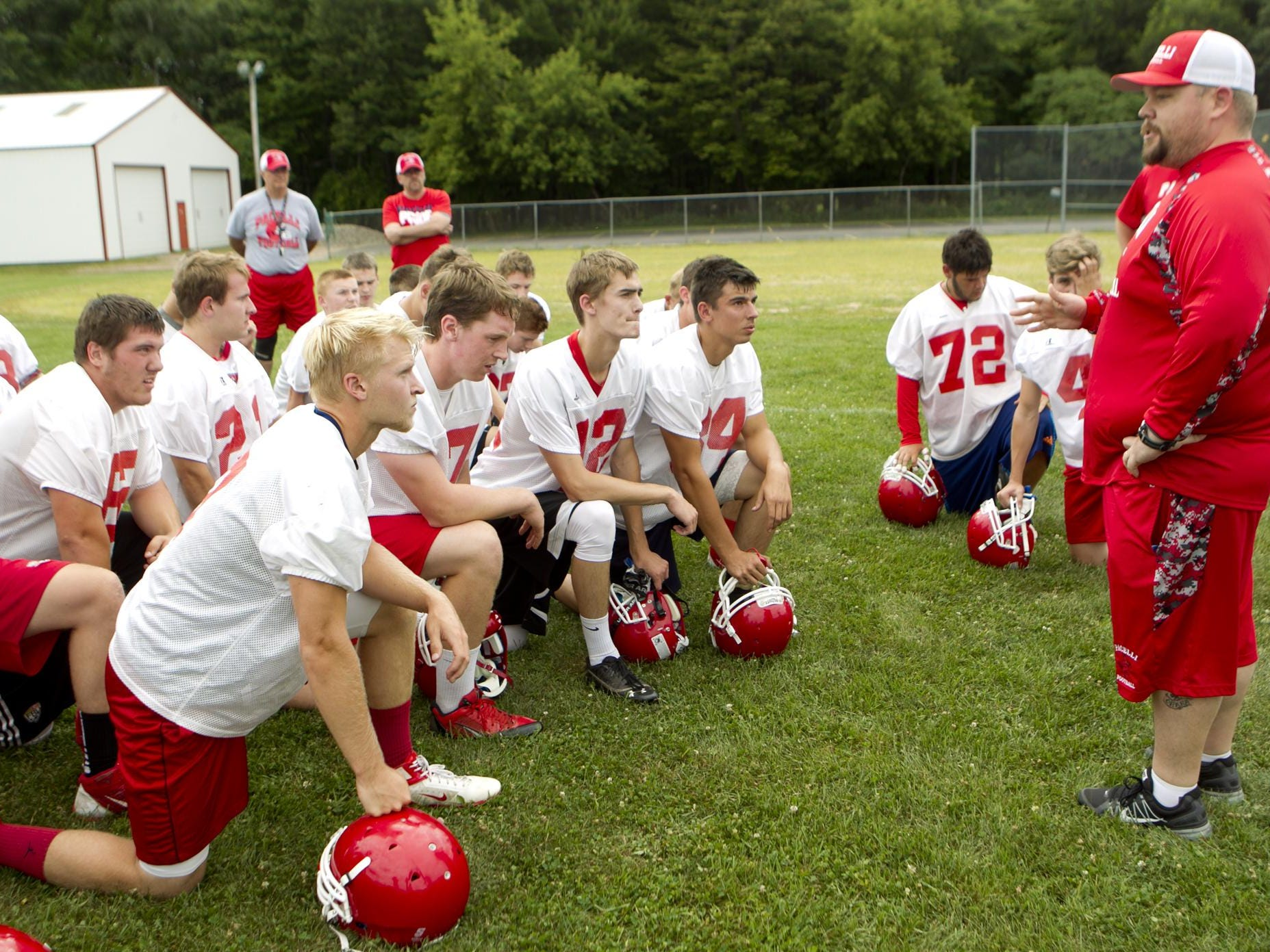 First-year Pacelli coach Drew Nelson addresses the football players on the first day of practice at Pacelli High School, Tuesday, Aug. 4, 2015.