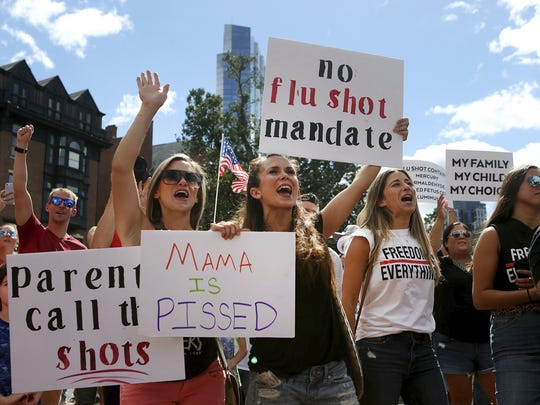 Maria Harvey and her sister Ashley Makridakis hold up signs during a protest against mandatory flu vaccinations, outside the Massachusetts State House, Sunday, Aug. 30, 2020, in Boston. Public health authorities say flu shots are very important this year to avoid overburdening the health system. amid the coronavirus pandemic.