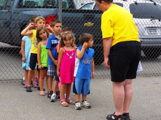 Miss Carol explains to the new bus riders how to wait for the driver's signal before crossing, in this image from 2010's event.