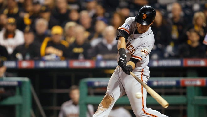San Francisco Giants second baseman Joe Panik singles against the Pittsburgh Pirates during the eighth inning of the 2014 National League Wild Card playoff baseball game at PNC Park. The Giants won 8-0.