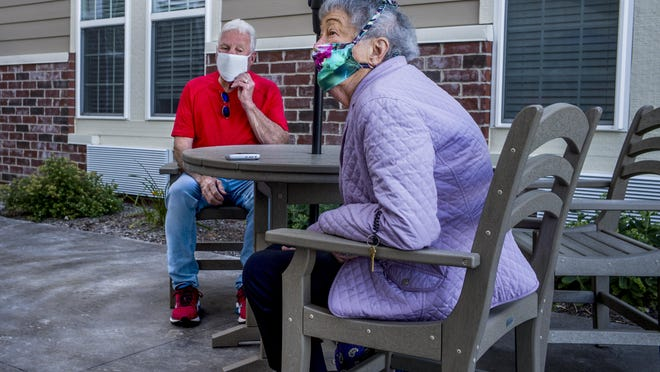 Jim McCarty, 77, adjusts his mask Thursday, June 25, 2020 during his first face-to-face visit in three months with his sister, Phyllis Mervosh, 86, at Serenity Assisted Living and Memory Care where she resides in East Peoria. While McCarty has communicated electronically often and seen his sister through the glass doors, state officials opened in-person visitations in long-term care facilities with restrictions.