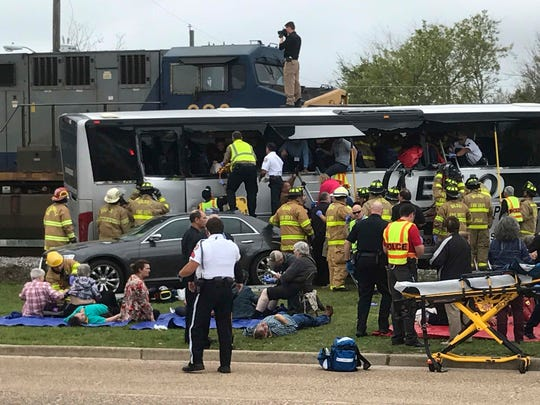 FILE - In this March 7, 2017, file photo, firefighters assist injured passengers after their charter bus collided with a train in Biloxi, Miss. Investigators say local Mississippi officials and CSX Corp. were well aware of trouble at the railroad crossing. But that information doesn't appear to have been reflected in a GPS mapping system that led the driver to the Biloxi crossing where 26 other vehicles had snagged on a steep hump in the previous five years. The National Transportation Safety Board is scheduled to meet Tuesday, Aug. 7, 2018, and release safety recommendations. (John Fitzhugh/The Sun Herald via AP, File)