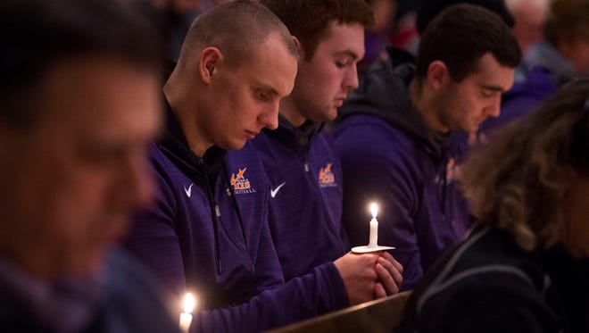 University of Evansville basketball player Dainius Chatkevicius holds a candle as he sits with his team during the 40th Anniversary Commemoration of the 1977 UE Plane Crash at Neu Chapel in Evansville, Ind., on Wednesday, Dec. 13, 2017.