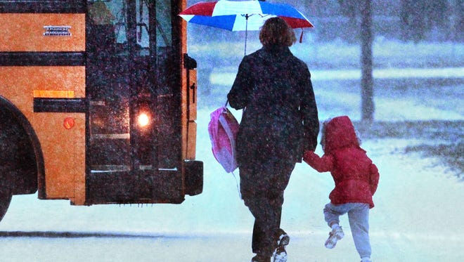 Kindergartener Katie Boyer, 5, holds tightly to the hand of her mother, Mary Boyer, as they walk to the school bus in their Far-Northside neighborhood in January 2013. Sunday, May 10, marks Mother's Day, a time to celebrate our mothers and all of the care-givers in our lives.