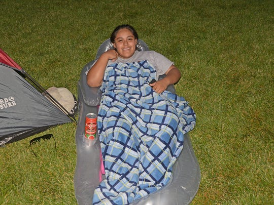Haley Chavez from Greeley relaxes while watching a movie at Boardwalk Park with her family.