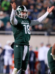Michigan State quarterback Connor Cook encourages the crowd during the fourth quarter of an NCAA college football game against Penn State, Saturday, Nov. 28, 2015, in East Lansing, Mich. Michigan State won 55-16.