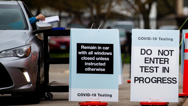 A person takes the self-administered nasal swab test April 20 from a rolling cart as staff stay at a safe distance at the Walgreens drive-thru COVID-19 testing facility at the former Walgreens location on North Ninth Street in Springfield.